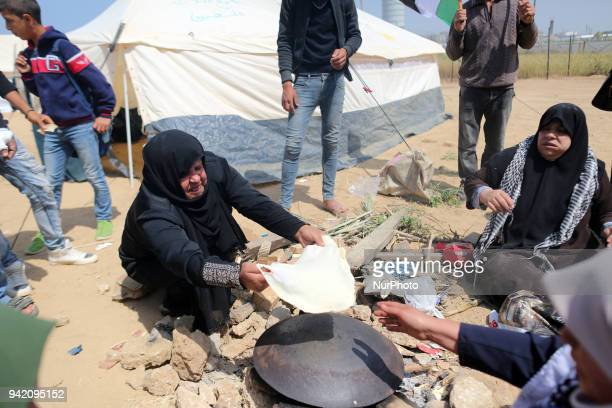 Women are baking bread at the Palestinian camp on the eastern border of the Gaza Strip on April 4 2018 next to near the border with Israel
