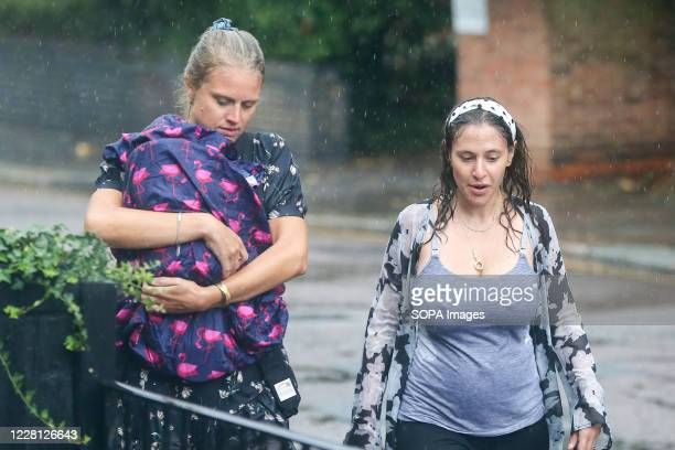 Women are caught in heavy rain as Storm Ellen brings rainfall with gusty winds in north London. According to the Met Office, warmer weather with...