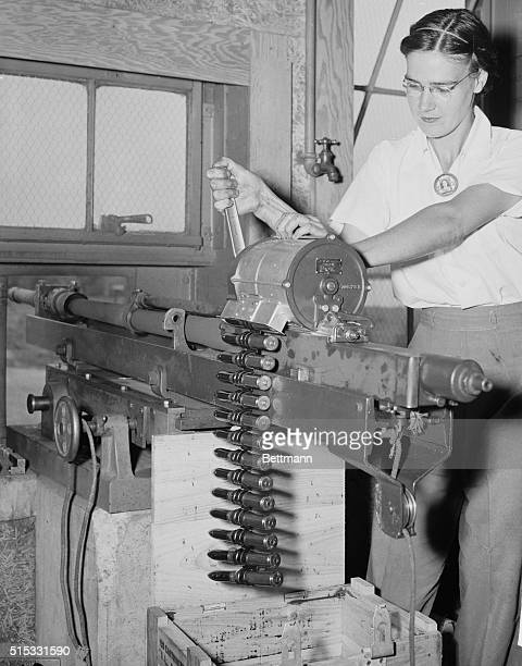 Women are doing their part to help Uncle Sam defeat the Axis and we see Mrs Mildred Thomas as she places a magazine on the 20mm airplane cannon There...