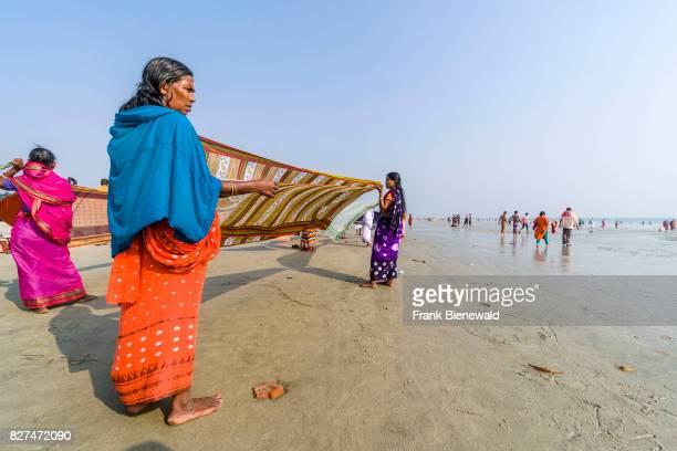 Women are drying her saris on the beach of Ganga Sagar celebrating Maghi Purnima festival