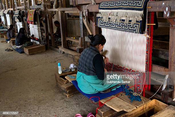 Women are engaged in weaving carpet in the traditional style at Tibetan Refugee Self Help Centre The Tibetan Refugee Self Help Centre of Darjeeling...