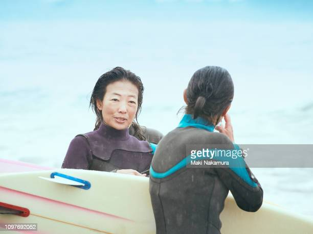Women are having fun at a beach with a surfboard