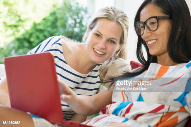 Women are looking at laptop, sitting on sofa.