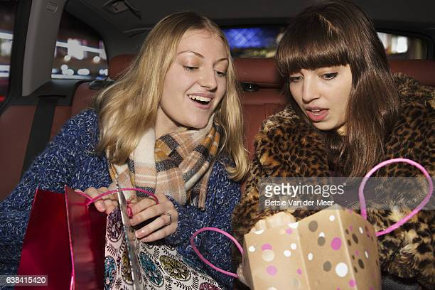 Women are looking at shopping in bag, sitting in taxi.