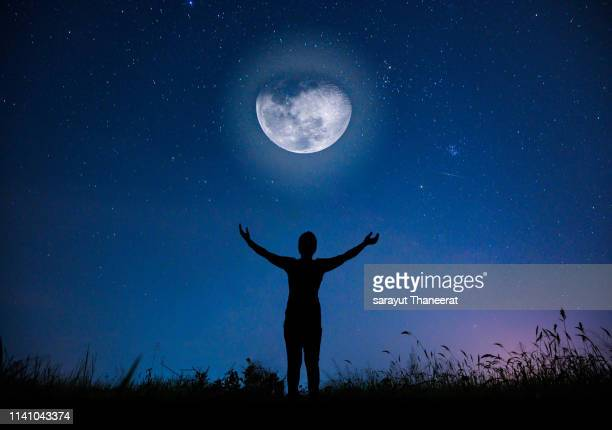 women are looking at the full moon on the night that the stars are full of sky. - astrology stock pictures, royalty-free photos & images