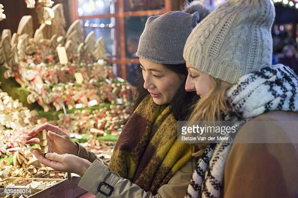 Women are looking at wooden christmas decoration at christmas market stall.