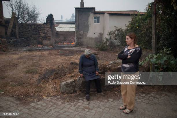 Women are seen after a wildfire burnt houses in the village of Vila Nova near Vouzela on October 16 2017 in Viseu region Portugal At least 30 people...