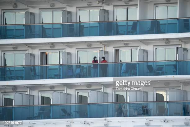 Women are seen on the balconies of the quarantined Diamond Princess cruise ship as it docks at Daikoku Pier on February 19 2020 in Yokohama Japan...