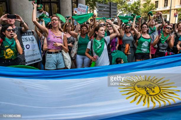 Women are seen protesting behind a huge Argentine flag 300 people mostly argentines and women gathered before the Consulate of Argentina in Barcelona...