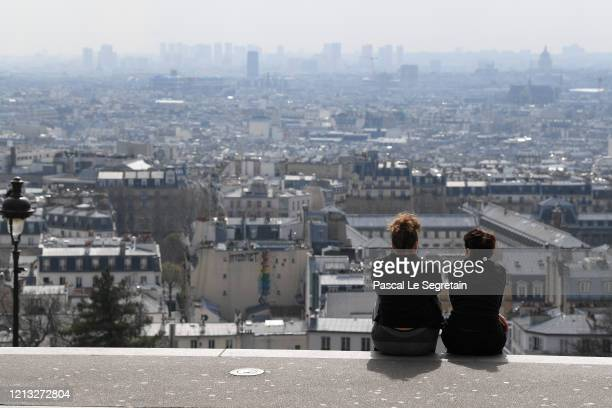 Women are seen sitting in Montmartre on the second day after the announcement by French President Emmanuel Macron of the confinement of the French...