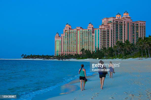 Women are walking barefoot on the beach of Paradise Island to the buildings of Atlantis Hotel while sunset on June 15 2012 in Nassau The Bahamas