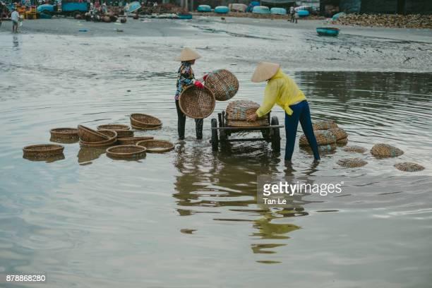 Women are washing bamboo basketry.