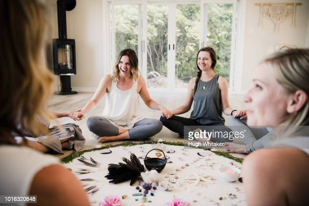 women around circle in yoga retreat - spirituality stock pictures, royalty-free photos & images