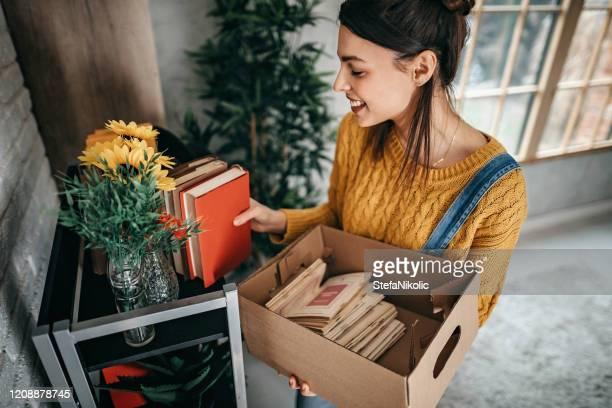 donne che organizzano cose in un nuovo appartamento - arrangiare foto e immagini stock