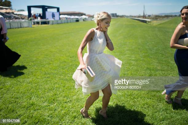 Women arrive to attend the Met horse race at Kenilworth race track on January 27 in Cape Town The Met is one of South Africa's premier horse races of...