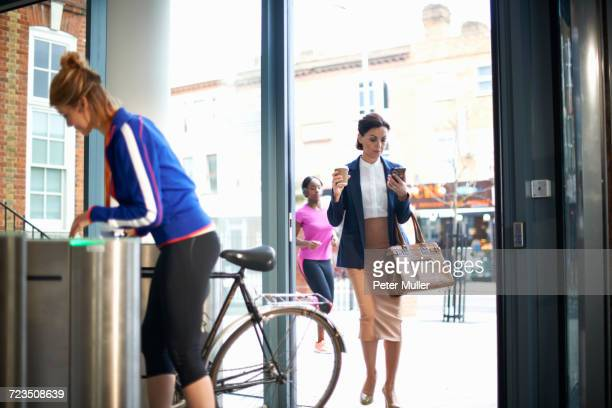 women arriving at entrance to work - bending over in skirt stock pictures, royalty-free photos & images