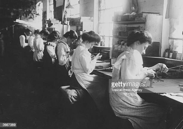 Women assembling radio equipment along a soldering bench at the Marconi Wireless and Telegraph Works Essex