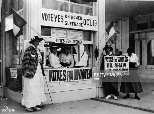 Women at a booth implore passersby to vote yes on women's suffrage at a vote to be held on October 19 New Jersey 1915 They are holding signs and...