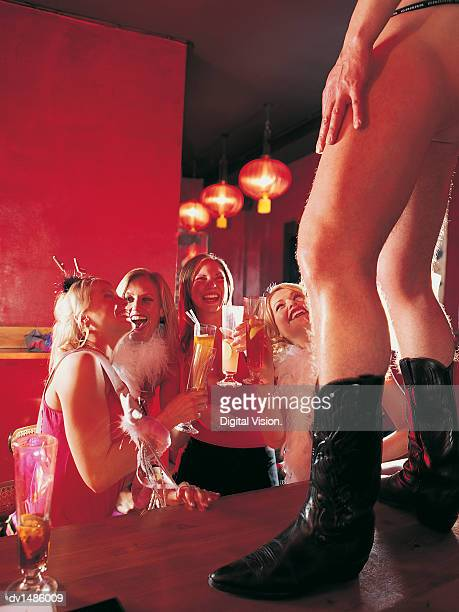 women at a hen night looking up at a male stripper standing on a bar counter - chippendales photos et images de collection