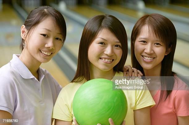 Women at bowling alley, smiling at camera