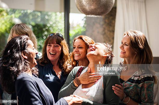 women at reunion greeting and smiling - wiedersehenstreffen stock-fotos und bilder