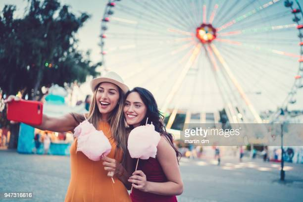 women at the amusement park eating pink cotton candy and taking selfie/vlogging - influencer stock pictures, royalty-free photos & images