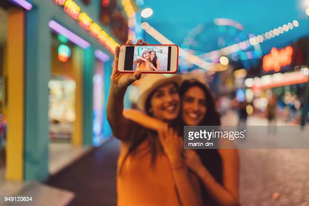 women at the amusement park taking selfie - ladies' night stock pictures, royalty-free photos & images