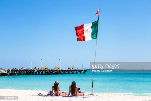 women at the beach near mexican flag, mexico - playa del carmen fotografías e imágenes de stock