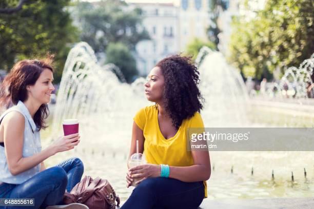 Frauen am Brunnen trinken Kaffee