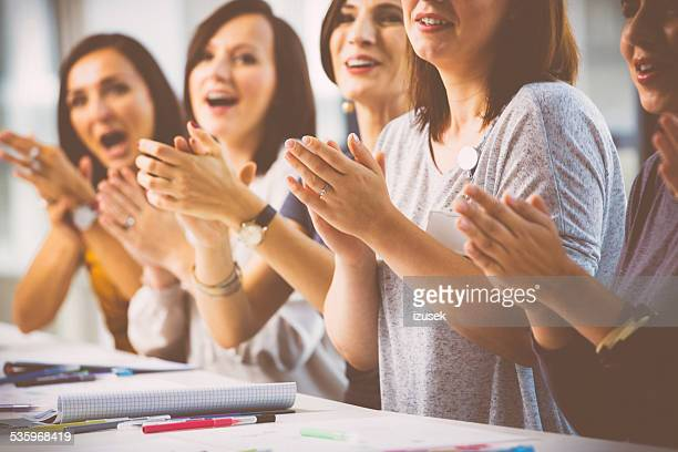 Women at the seminar clapping hand