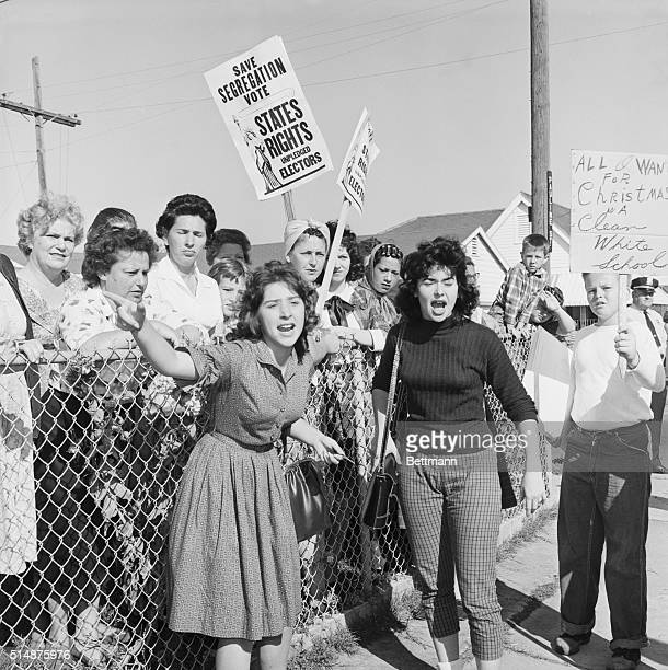 Women at William Franz Elementary School yell at police officers during a protest against desegregation at the school, as three black youngsters...
