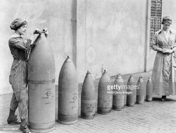 Munitions Production Chilwell Nottinghamshire England UK c 1917 Two women munitions workers stand beside examples of the shells produced at National...