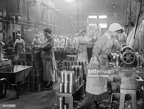 Women At Work During The First World War Women munition workers turning copper bands for artillery shells during the First World War at Royal Shell...