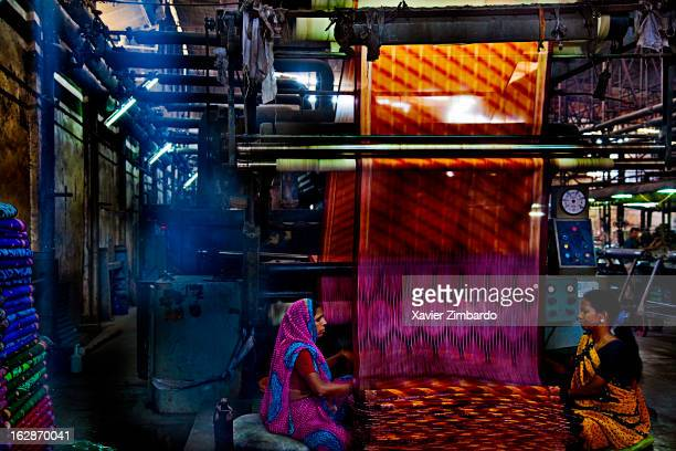 Women at work while raw cloth undergoes dyeing process at colour dyeing machine in Rajasthan India on April 5 2009