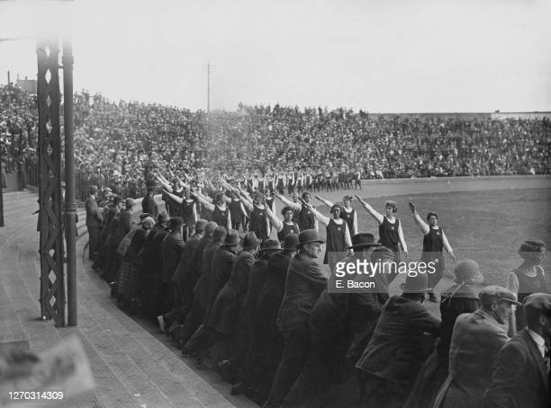 Women athletes salute the crowds at the Women's International and British Games, at Stamford Bridge in London, August 1924. They are all wearing a...