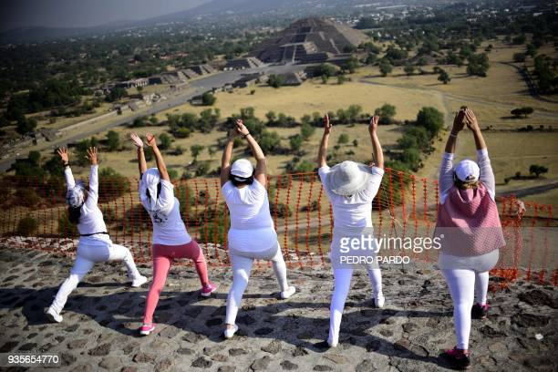 Women atop the Pyramid of the Sun at the archaeological site of Teotihuacan in the municipality of Teotihuacan northeast of Mexico City stretch and...
