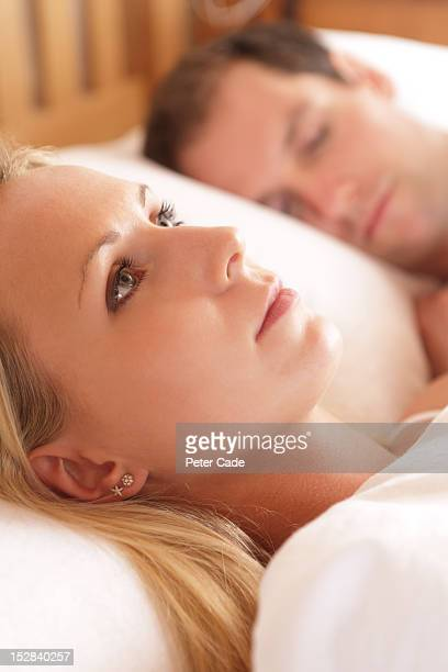 Women awake in bed next to sleeping partner