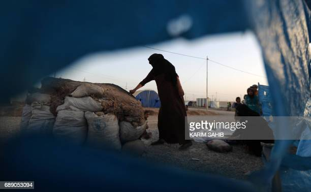 Women bake bread on the first fasting day of the Muslim holy month of Ramadan at alKhazir camp for the internally displaced located between Arbil and...