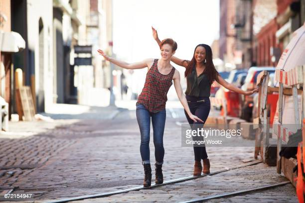 Women balancing on track in cobblestone city street