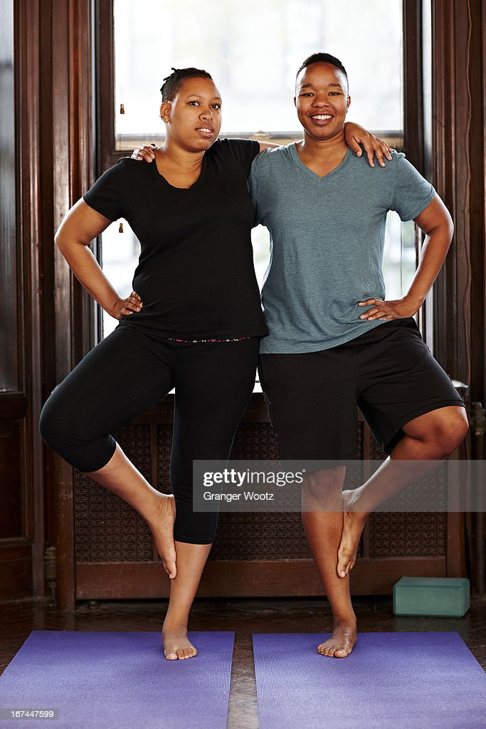 Women balancing together in yoga class : Stock Photo
