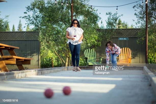 Women Balancing Wine Glasses While Playing Bocce