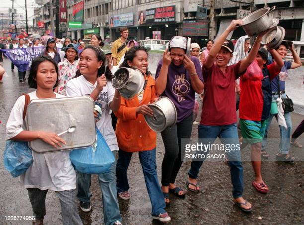"""Women bang pots and pans during a protest march of about 2,000 people to the Malacanang presidential palace 08 March in Manila against """"sexist""""..."""