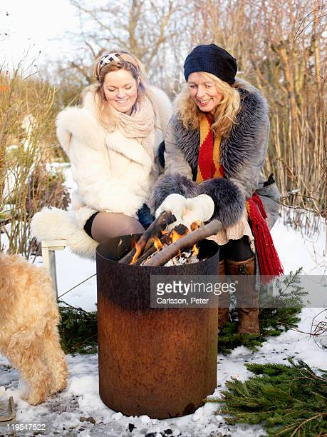 Women barbecuing in winter, smiling