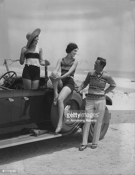 2 women bathing suits posed on convertible car with man in striped trousers and vest looking on upscale fashion wealth leisure straw hat. - 1920 car stock photos and pictures