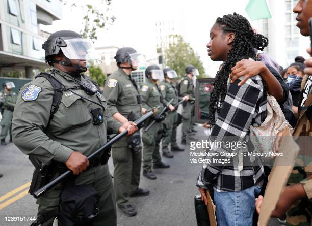 A women becomes emotional while talking to a Santa Clara County Police officer at a protest for the killing of George Floyd outside of San Jose City...