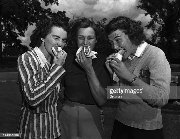 Dot Kielty of Los Angeles Mrs George Zaharias of Los Angeles and Betty Jean Rucker of Spokane Washington munch frankfurters after their second round...