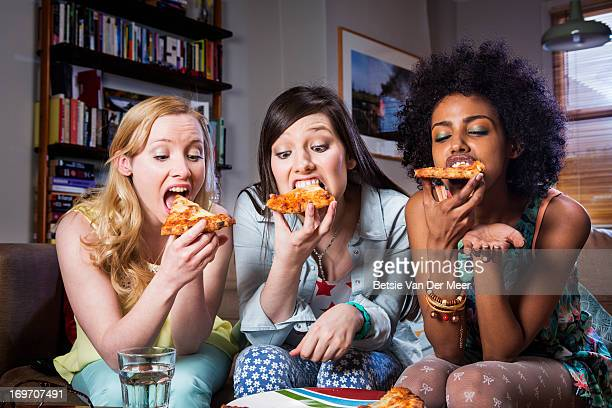 Women biting into pizza sitting together on sofa.
