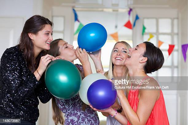 Women blowing up balloons together