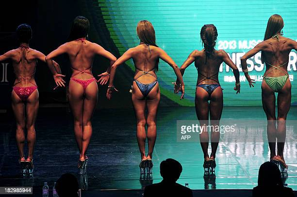 Women body builders pose in front of judges during the Muscle Mania Fitness Korea Competition in Seoul on October 3 2013 Successful participants will...