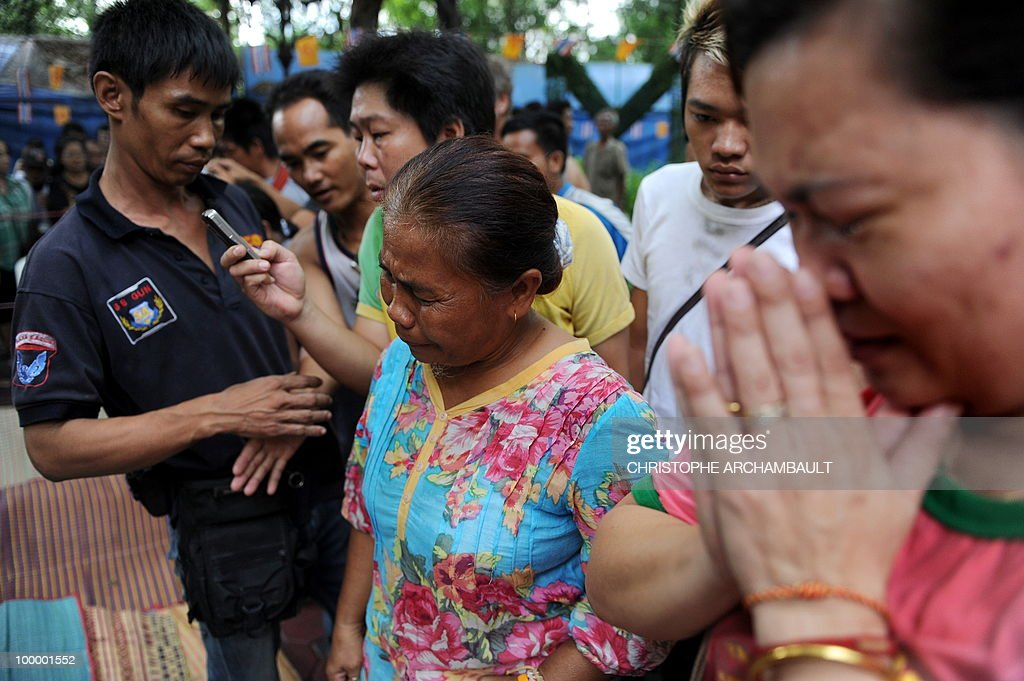 Women break down as they gather beside the dead bodies of anti-government protesters killed in a gunbattle the day before at a temple which had been turned into a shelter within an anti-government protest site in downtown Bangkok on May 20, 2010. Gunshots rang out near a Buddhist temple in the heart of an anti-government protest zone in Bangkok, and soldiers were advancing on foot along an elevated train track, an AFP photographer saw. Thai security forces stormed the 'Red Shirts' protest camp on May 19 in a bloody assault that forced the surrender of the movement's leaders who asked their supporters to disperse. AFP PHOTO/Christophe ARCHAMBAULT